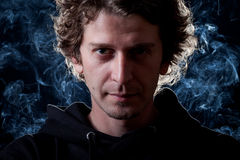 Young man portrait. Young curly hair caucasian man wearing black hooded sweatshirt. Low key portrait taken on black background full of smoke Stock Photography