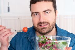 Young man portrait dieting and eating fresh salad stock photography