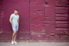 Young man portrait in front of brick wall. Portrait of confident serious hot guy wearing casual clothing walking on the street beside old red brick wall, looking Royalty Free Stock Image