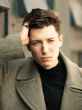 The young man poses in a coat.close up, image toned Royalty Free Stock Photo
