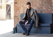 The young man poses in a coat sitting on a bench Royalty Free Stock Photography