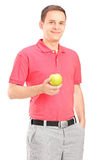 Young man posing with an apple in his hand Stock Photos