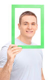Young man posing behind a green picture frame Royalty Free Stock Photo