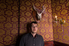 Young Man Posing Beneath Antlered Deer Skull Stock Photo