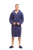 Young man posing in a blue bathrobe Stock Images