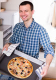 Young man posing with delicious pizza. Young happy man posing with delicious pizza Royalty Free Stock Images