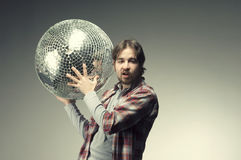 Young man posing with a disco ball Royalty Free Stock Images