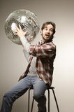 Young man posing with a disco ball Royalty Free Stock Photo