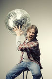 Young man posing with a disco ball Stock Photography