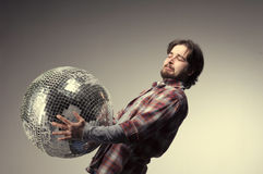 Young man posing with a disco ball Royalty Free Stock Image