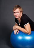 Young man posing with exercise ball Royalty Free Stock Images