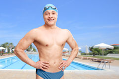 Young man posing in front of a swimming pool. Young man with a swimming cap and goggles posing in front of a swimming pool and smiling stock image