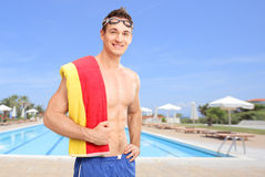 Young man posing in front of a swimming pool Royalty Free Stock Image