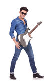 Young man posing with guitar. Full length photo of a casual young man posing with an electric guitar and smiling to the camera Royalty Free Stock Image