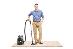 Young man posing next to a vacuum cleaner Royalty Free Stock Image