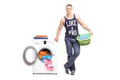 Young man posing next to a washing machine Royalty Free Stock Image
