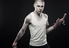 Young man posing with nunchaku Royalty Free Stock Photography