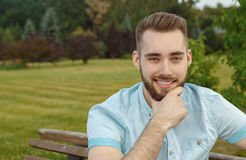 Young man posing on park bench Stock Photo