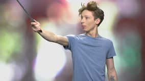 Young man posing for photo. Funny teenage boy with crazy hair using selfie stick on abstract blurred background. People, modern technology and fun stock video footage