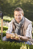 Young man posing with potatoes in garden Stock Image