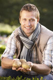Young man posing with potatoes in garden Stock Images