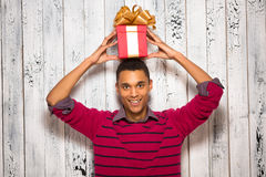 Young man posing with a present in studio Royalty Free Stock Photography