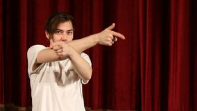 Young man posing pretending shooting with finger-guns against red curtain background.  stock footage