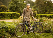 Young man posing with retro motorbike in the park. Royalty Free Stock Photography