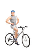 Young man posing seated on a bicycle Royalty Free Stock Photos