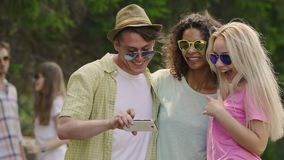 Young man posing for selfie with two female friends, happy people laughing. Stock footage stock video