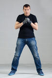 Young man posing in studio with working gloves Royalty Free Stock Image