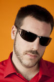 Young man posing with sunglasses on orange backgro Stock Photo