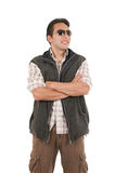 Young man posing wearing sunglasses and vest. Latin man posing crossed arms wearing sunglasses and vest isolated over white Royalty Free Stock Image