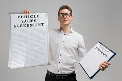 Young man holding a vehicle sales agreement and blank contract form on a light background. Young man with a poster vehicle sales agreement is and blank contract stock image