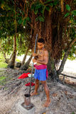 Young man pounding kava roots in Lavena village, Taveuni Island,. Fiji. The roots are used to produce a drink with sedative, anesthetic, euphoriant, and Stock Photo