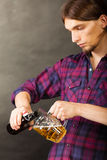 Young man pouring beer from bottle into mug Royalty Free Stock Photography