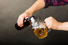 Young man pouring beer from bottle into mug Stock Photo