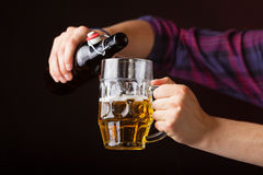 Young man pouring beer from bottle into mug Royalty Free Stock Images