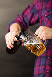 Young man pouring beer from bottle into mug Royalty Free Stock Image
