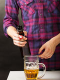 Young man pouring beer from bottle into mug Stock Photography
