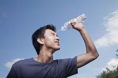 Young Man Pouring Bottled Water Over His Head Royalty Free Stock Photography