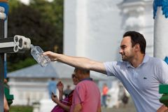 Young man pouring the holy water in a bottle from the Holy spring Royalty Free Stock Photo