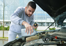 Young man pouring oil into the car. Young man adding oil into the car Stock Photography