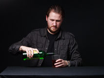 Young man is pouring out alcohol from the bottle to the winegla stock images