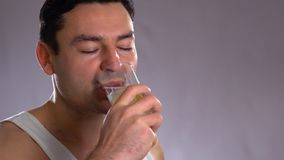 Young man pouring water from bottle to water in kitchen stock footage