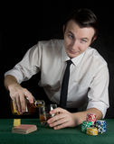 Young man pouring whiskey at the casino table. Young bartender pouring whiskey at the casino table whith deck of cards and chips Stock Photos