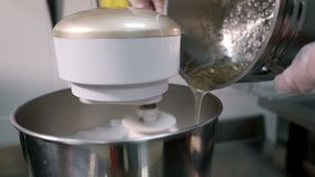 Young man pours sugar mixture into bowl with working mixer in kitchen. stock footage