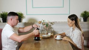 Man pours tasty tea into woman cup in cozy modern cafe. Young man pours tasty fresh aromatic tea into happy woman cup sitting at wooden table in modern cozy cafe stock footage