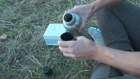 A young man pours tea from a thermos in the open air stock video footage