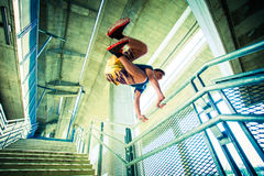 Young man practice parkour jump in the city. Young man practice parkour jump on stairs with metal fence in the city extreme sport concept shot from from below royalty free stock photography